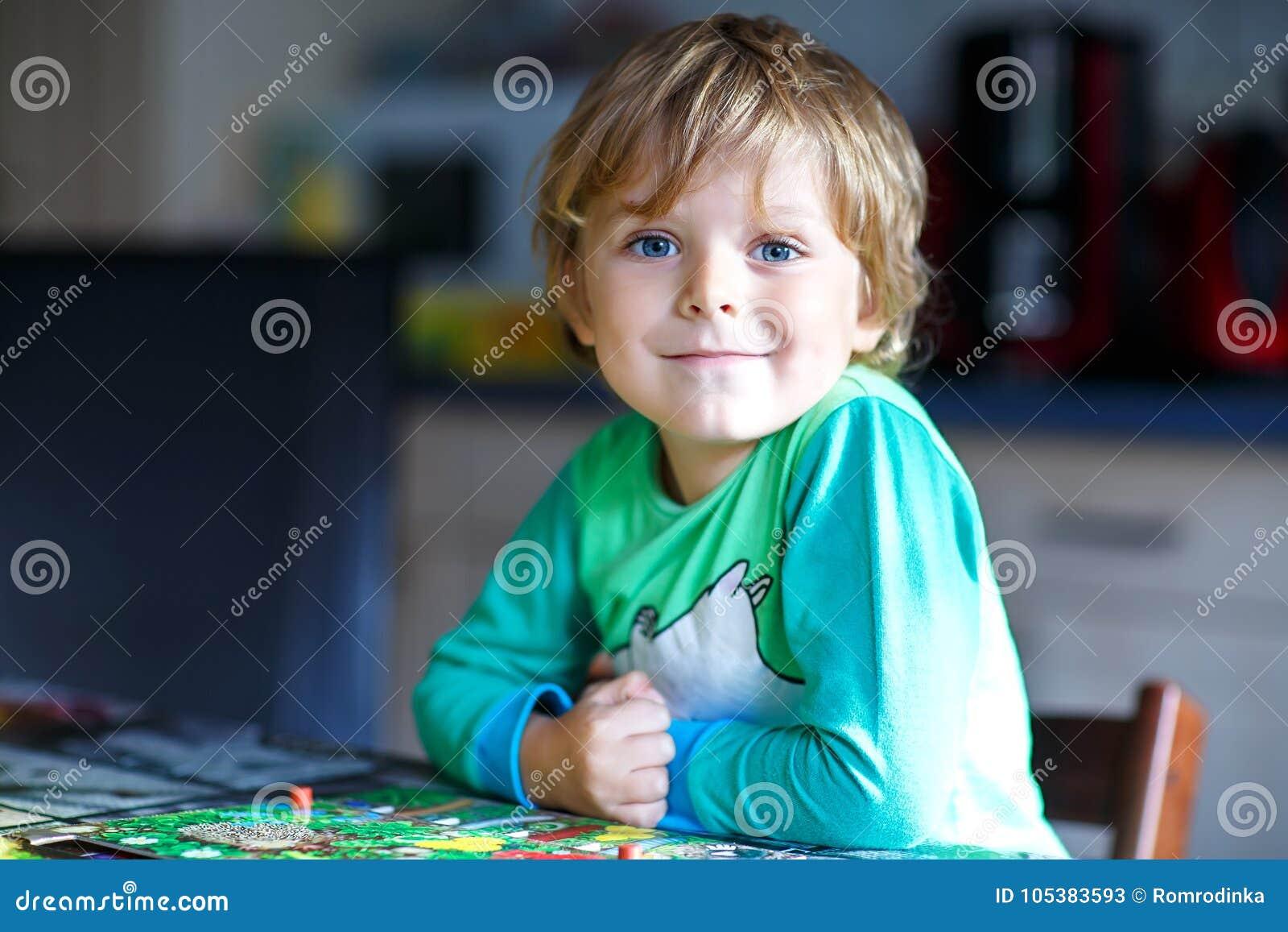 Kleiner blonder Kinderjunge, der zusammen zu Hause Brettspiel spielt Lustiges Kind, das Spaß hat