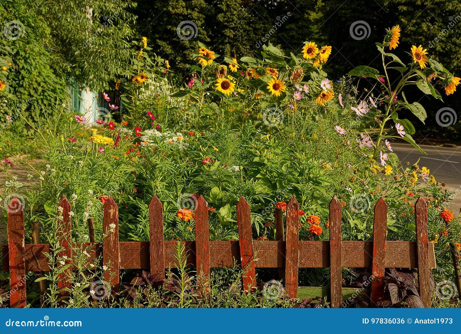 Kleiner Dekorativer Brauner Zaun Vor Einem Blumenbeet Stockfoto