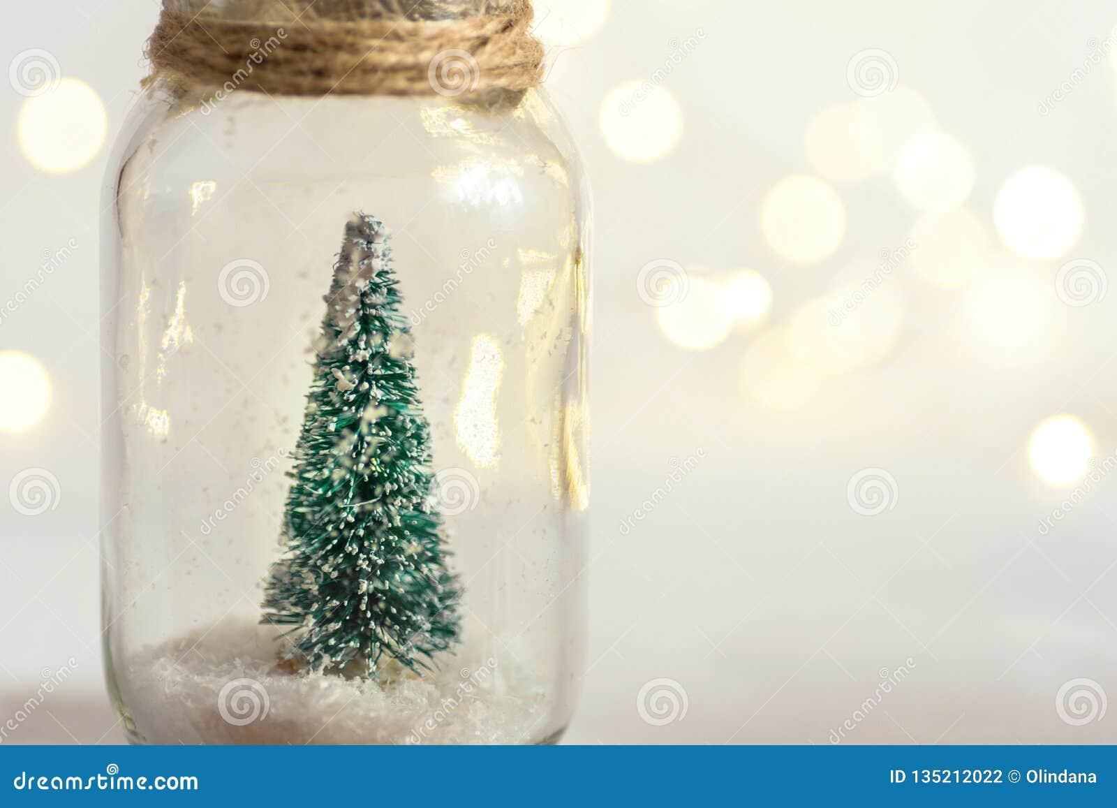 Kleiner dekorativer Weihnachtsbaum im Glasgefäß gebunden mit Schnur Bokeh Girlande des Schnees goldenes funkelnde Lichter Grußkar
