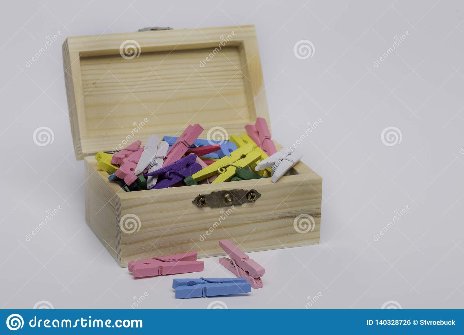 Kleiner hölzerner Kasten mit farbigen Klammern