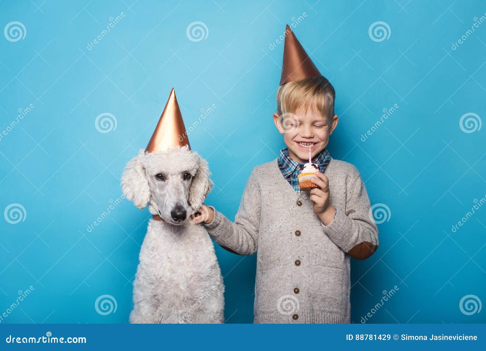 Kleiner hübscher Junge mit Hund feiern Geburtstag Freundschaft Liebe Kuchen mit Kerze Studioporträt über blauem Hintergrund
