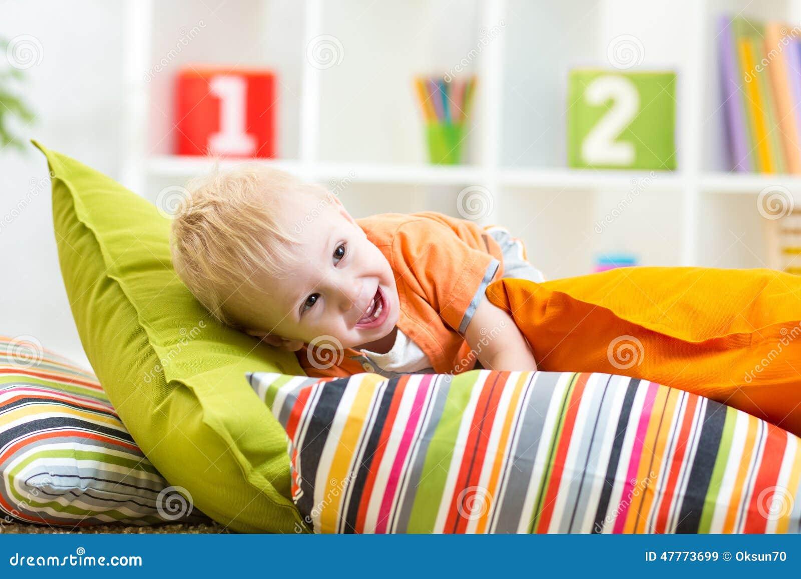 Kleiner junge der auf kissen im schlafzimmer spielt for Schlafzimmer junge