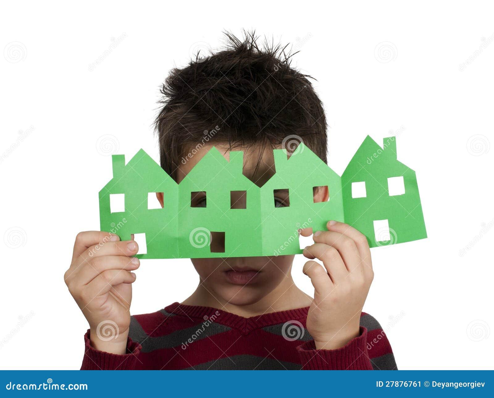 Kleiner Junge, der Häuser gemacht vom Papier hält