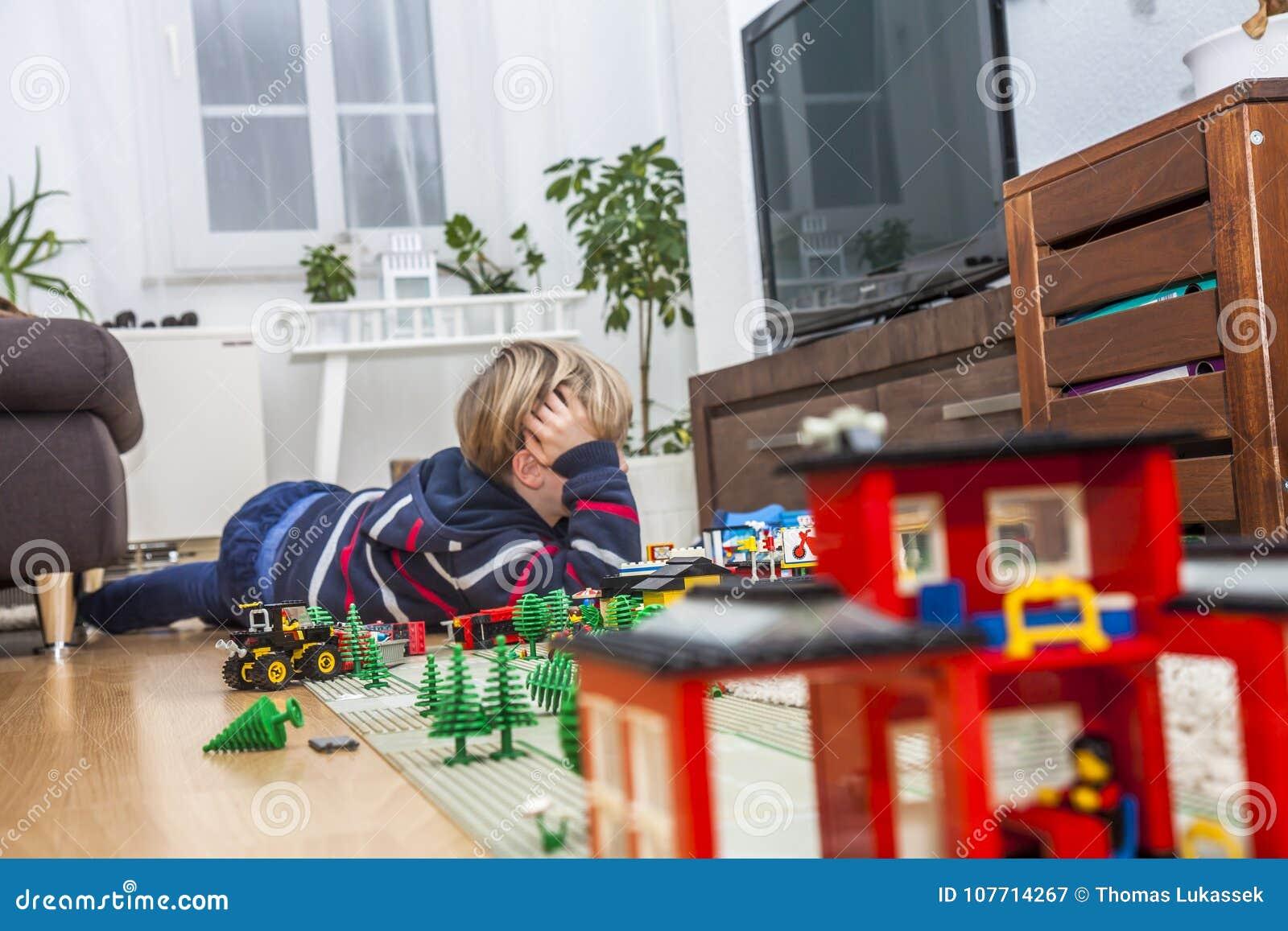 Kleiner Junge, der mit Ziegelsteinen auf dem Boden spielt