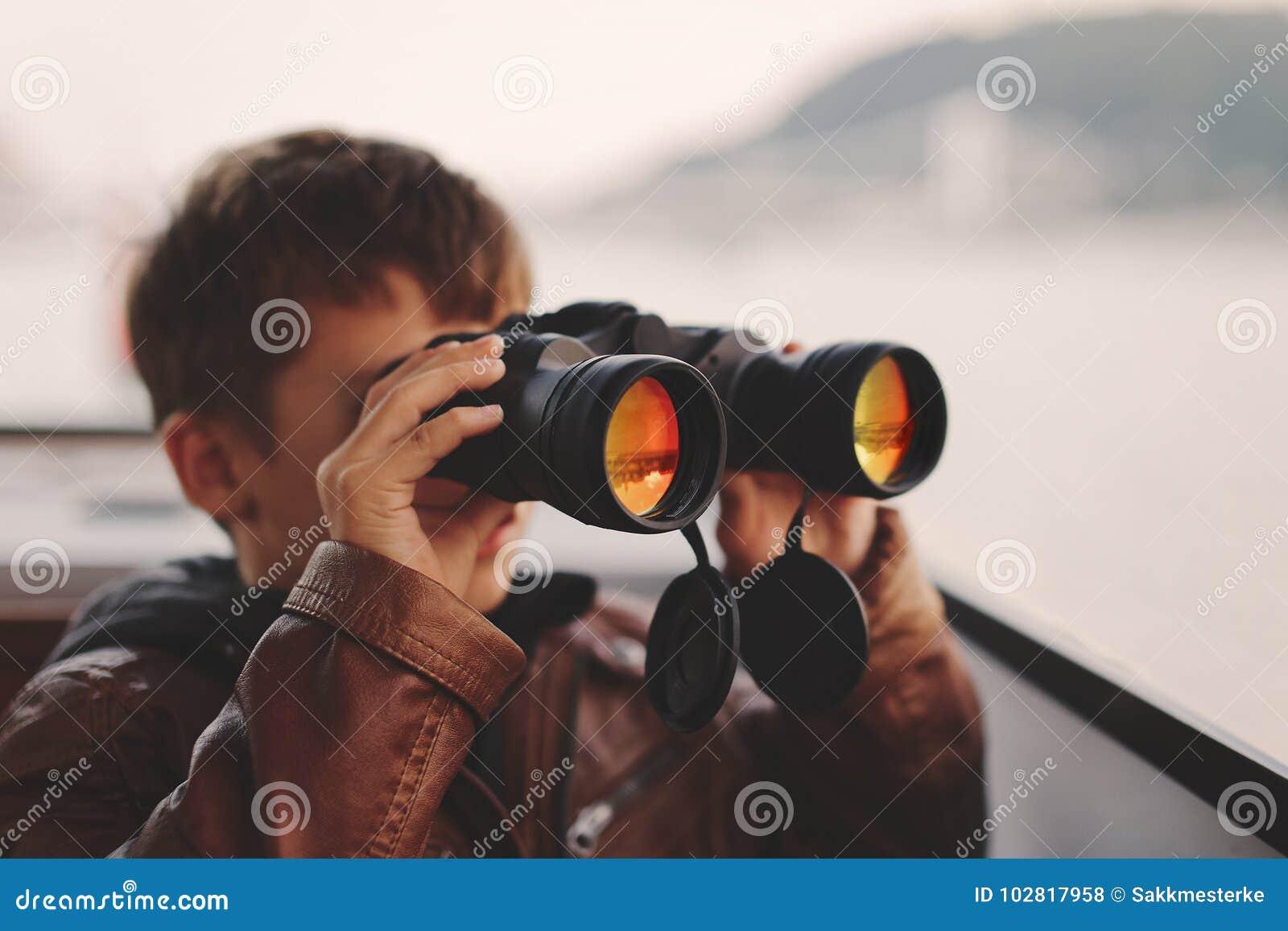 Kleiner Junge, der, schauend, Anstarren aufpasst und suchen nach durch binokularem