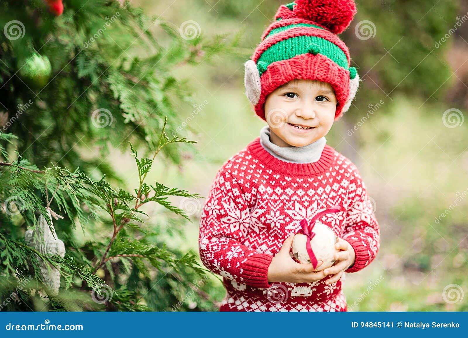 Kleiner Junge in der Strickjacke und in Hut, die auf ein Weihnachten im Holz warten