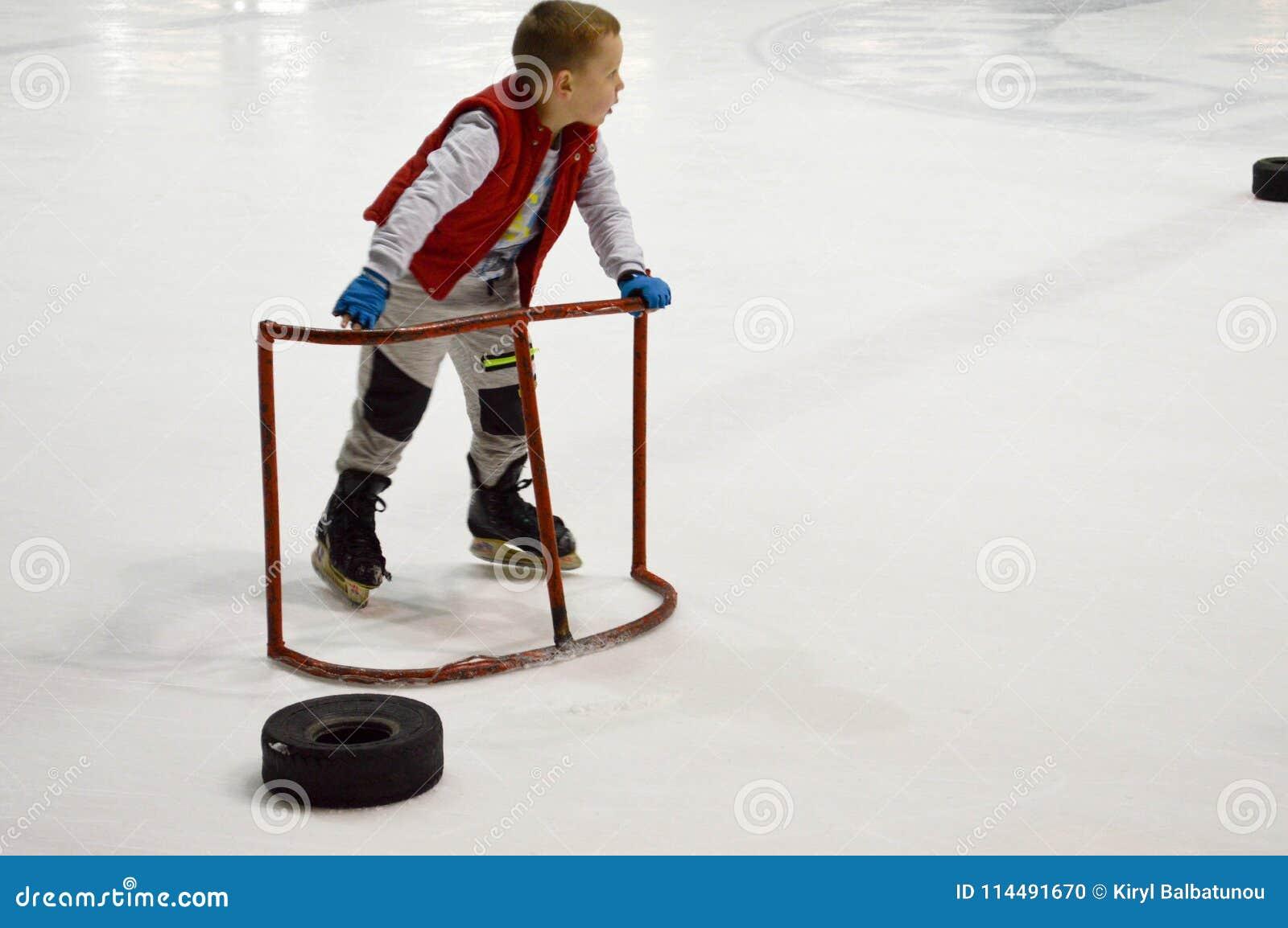 Kleiner Junge lernt, mithilfe der speziellen Unterstützungstore auf der Eishockeyarena eiszulaufen am 14. April 2018 Weißrussland