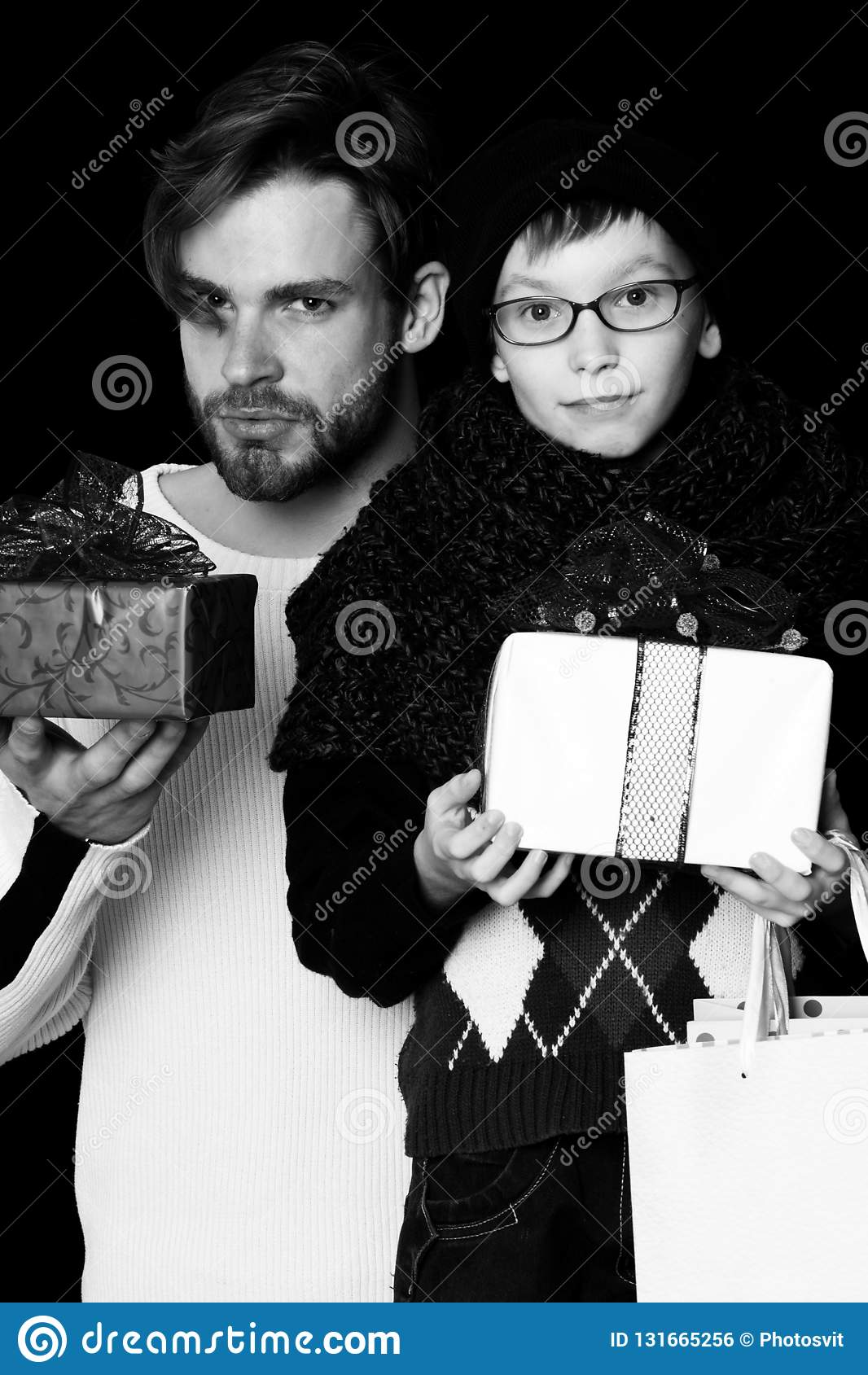 Kleiner Junge oder nettes Sonderlingskind in den Gläsern, Hut und moderner gestrickter Schal und gut aussehender Mann oder bärtig