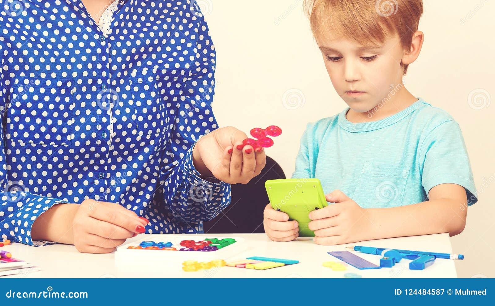 Kleiner Junge spielt logisches Spiel an der Lektion eines Psychologe Smart-Kindes mit dem Lehrer, der am Vorschulklassenzimmer le
