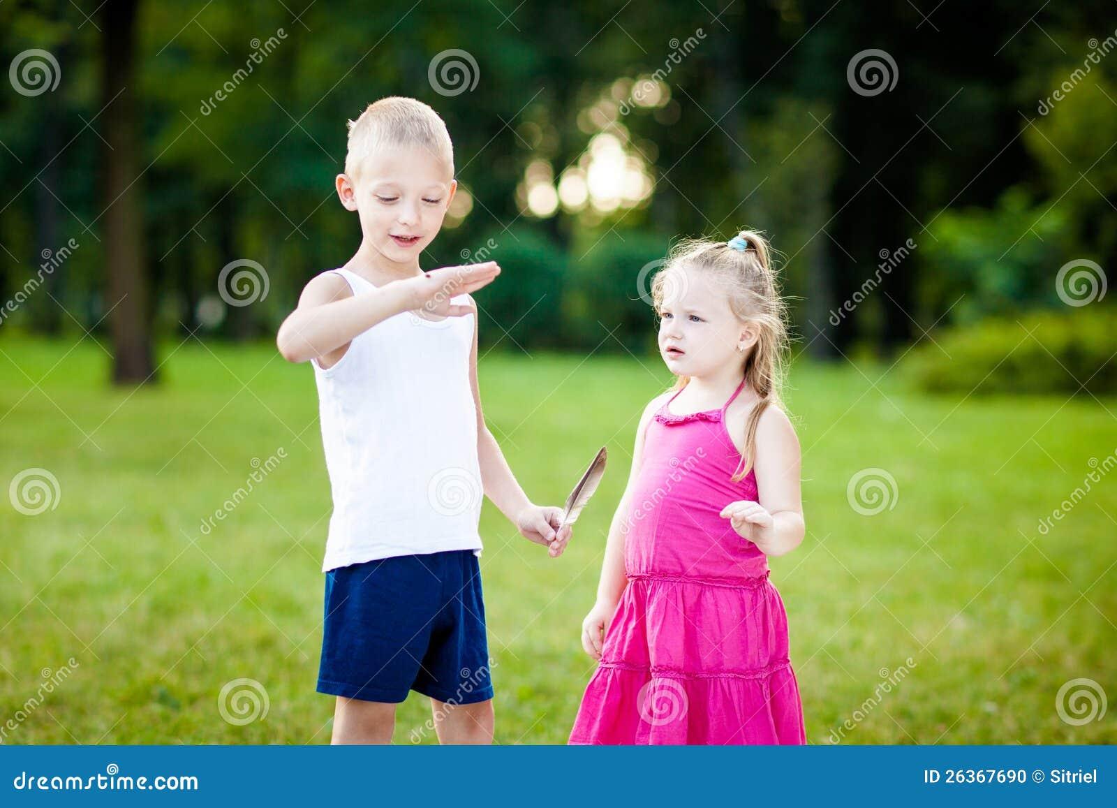 Kleiner Junge und Mädchen mit Marienkäfer im Park