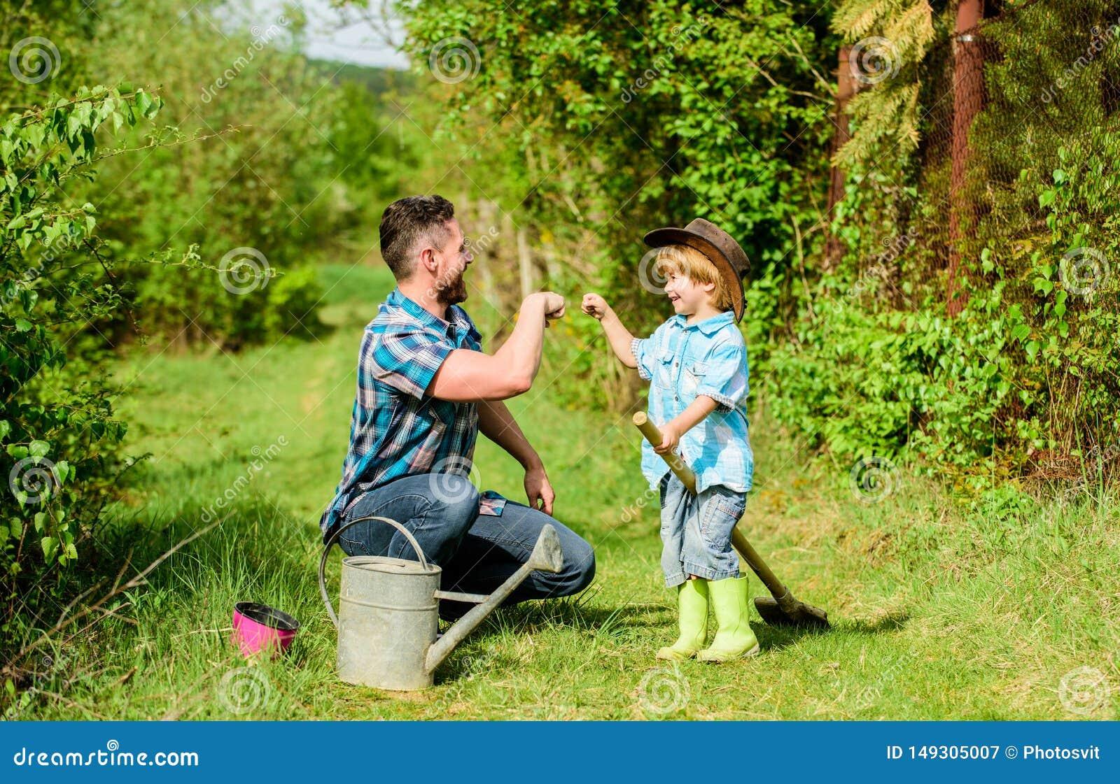 Kleiner Jungenkinderhilfsvater bei der Landwirtschaft Eco-Bauernhof Vater und Sohn im Cowboyhut auf Ranch Benutzen Sie Gie?kanne