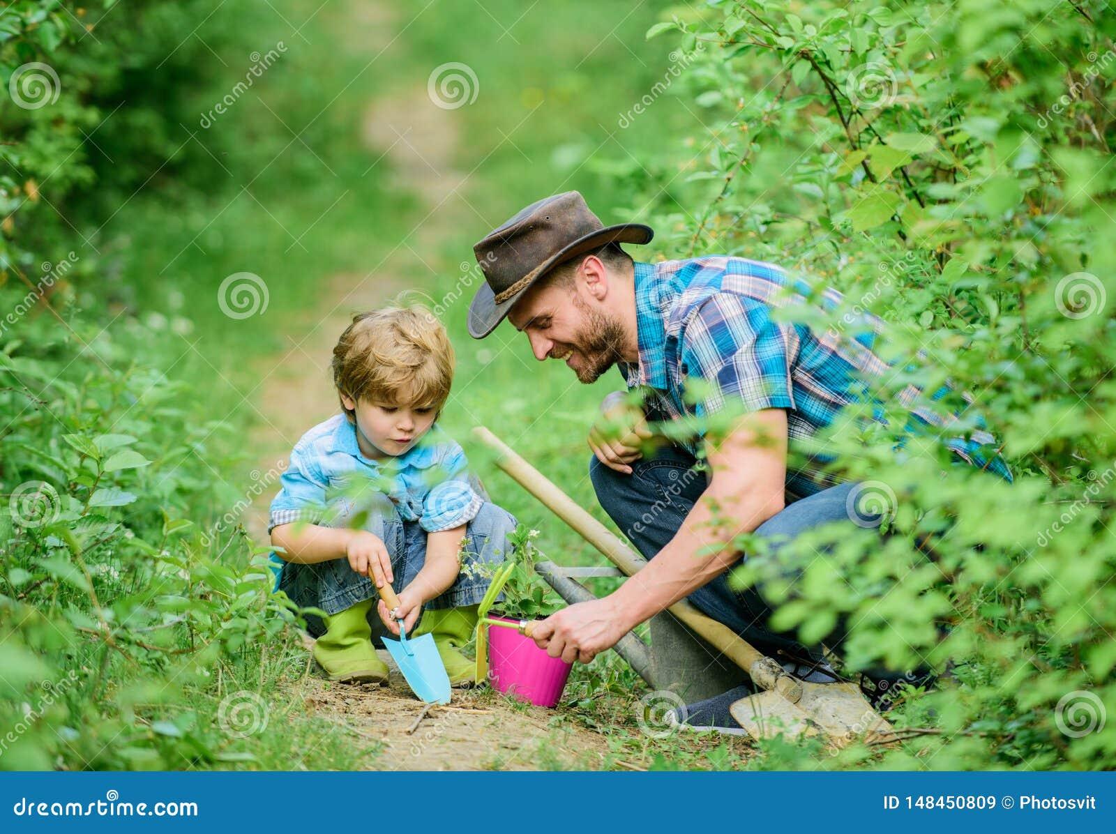 Kleiner Jungenkinderhilfsvater bei der Landwirtschaft Eco-Bauernhof Vater und Sohn im Cowboyhut auf Ranch Hacke, Topf und Schaufe