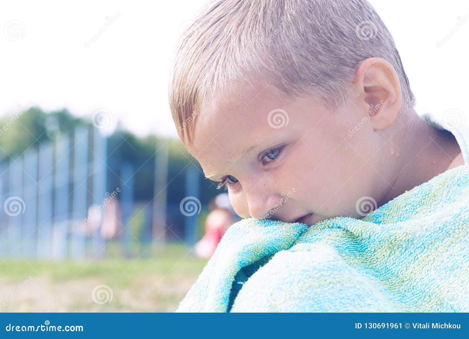 Kleiner kaukasischer Junge, der nach Schwimmen im See sich aalt Der Junge bedeckte sich mit dem Tuch und sitzt auf dem Ufer von