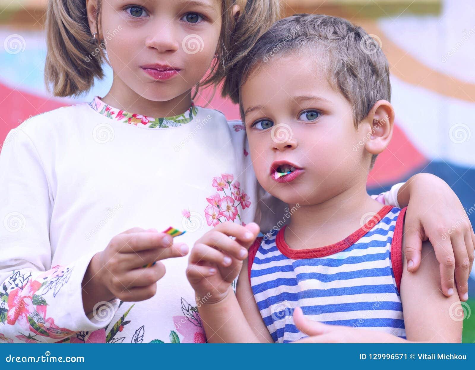 Kleiner kaukasischer Junge und ein Kaugummi des Mädchens bei der Stellung auf dem Spielplatzarm im Arm Bild von den glücklichen F