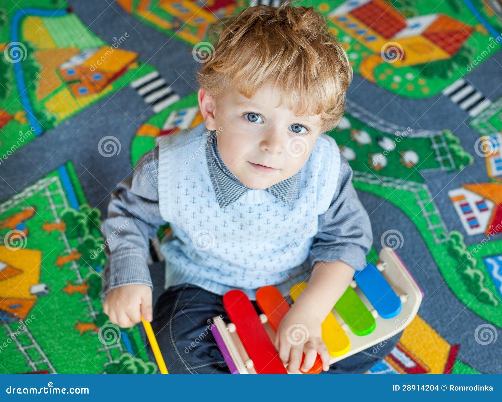 Kleiner Kleinkindjunge, der mit hölzernem Musikspielzeug spielt