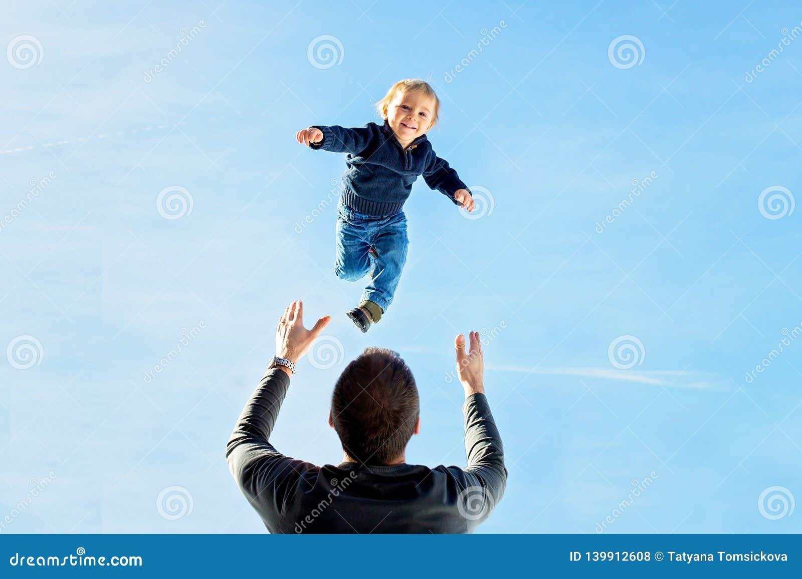 Kleiner Kleinkindjunge, fliegend in den Himmel, Vati, der ihn hoch in der Luft wirft Familie, Winteransicht von schneebedeckten B