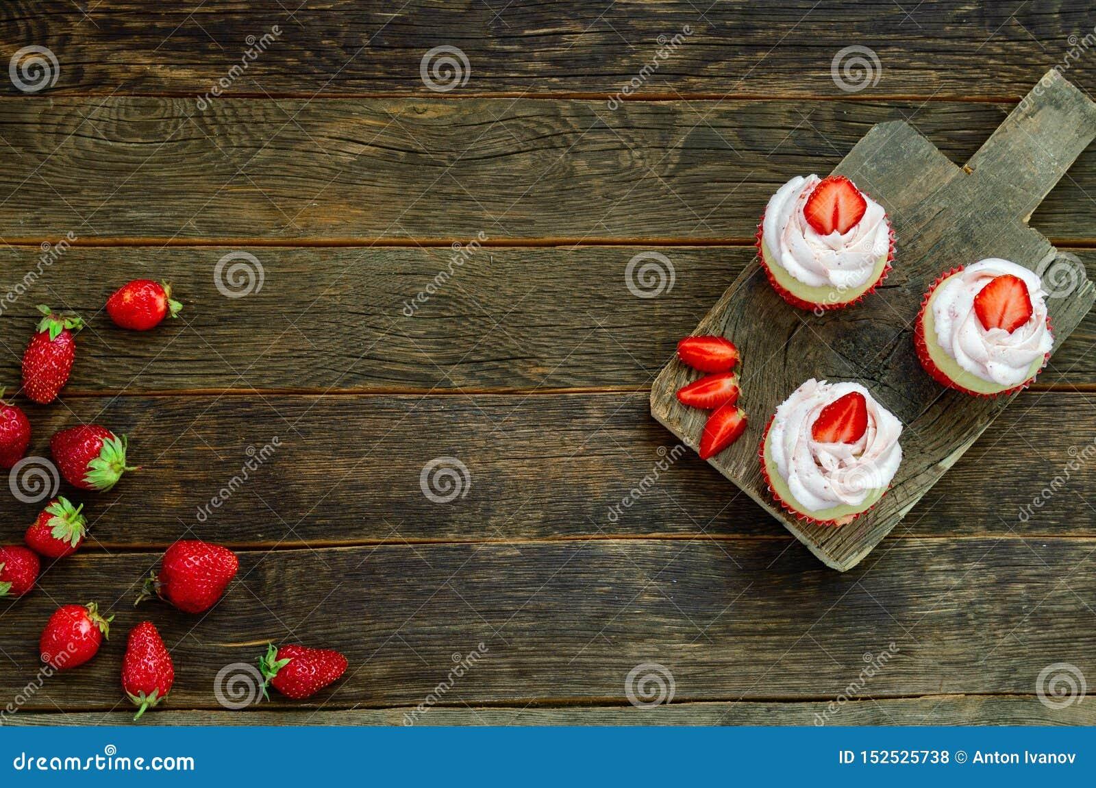 Kleiner Kuchen mit Wunderkerze auf Tabelle auf hölzernem Hintergrund