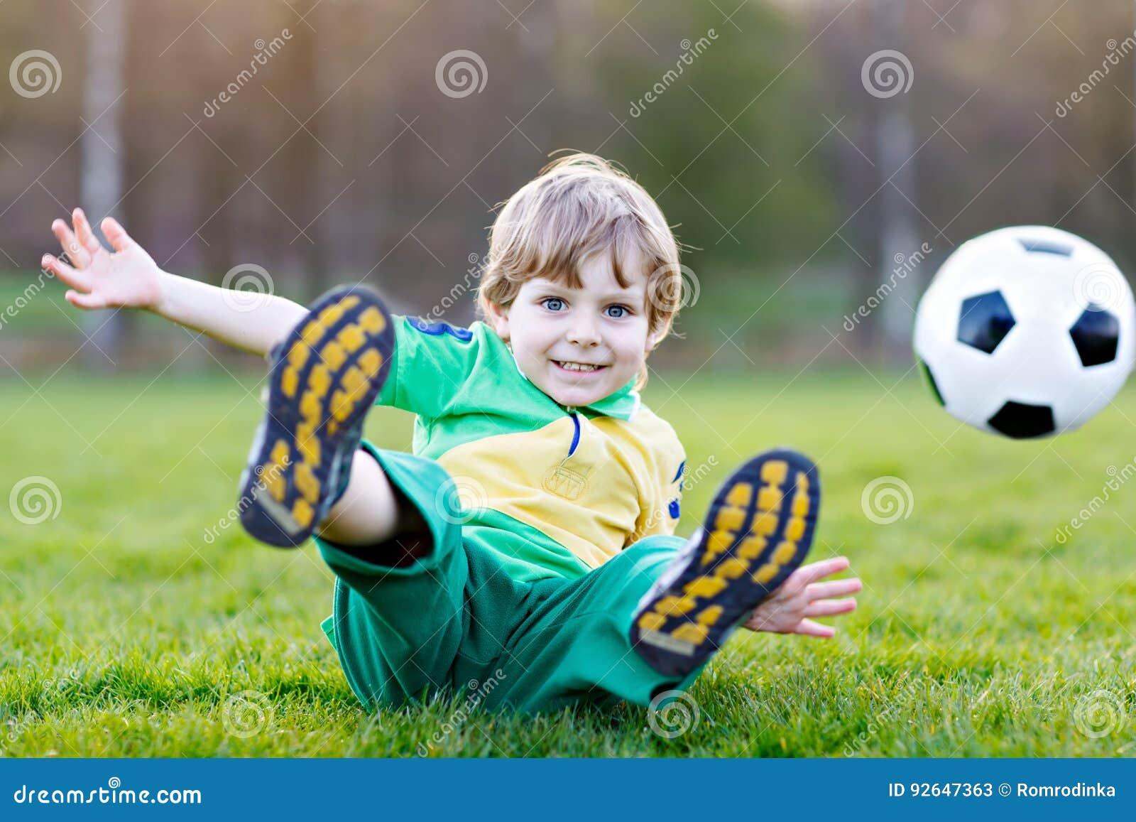 Kleiner netter Kinderjunge spielenden Fußballs 4 mit Fußball auf Feld, draußen
