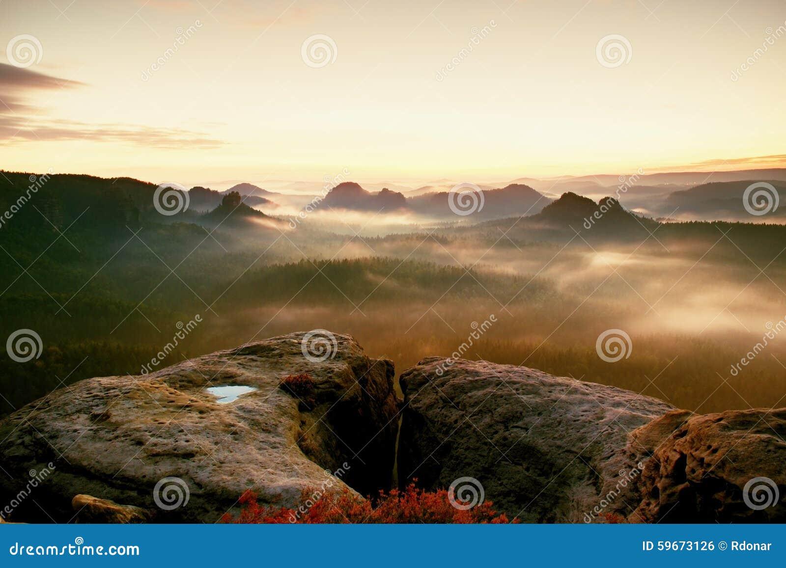 Kleiner Winterberg sikt Fantastisk drömlik soluppgång på överkanten av det steniga berget med sikten in i den dimmiga dalen