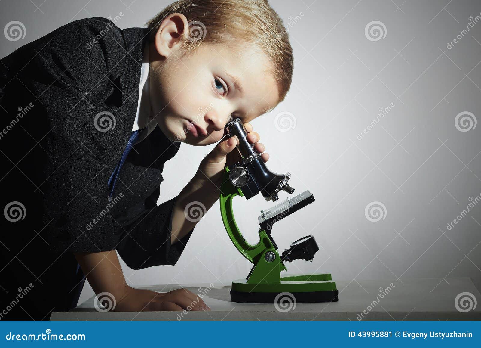 Kleiner wissenschaftler der im mikroskop schaut little boy kind