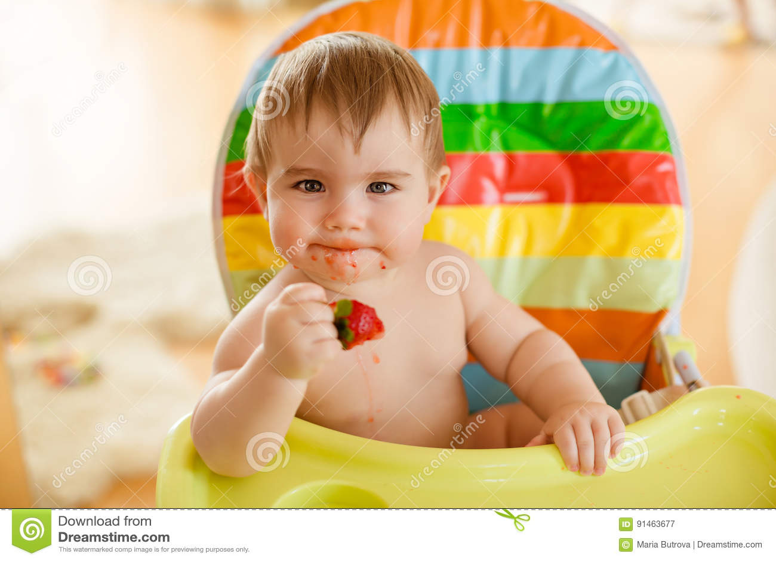 Kleines Baby Das In Einem Hellen Stuhl Erdbeeren Essend Sitzt