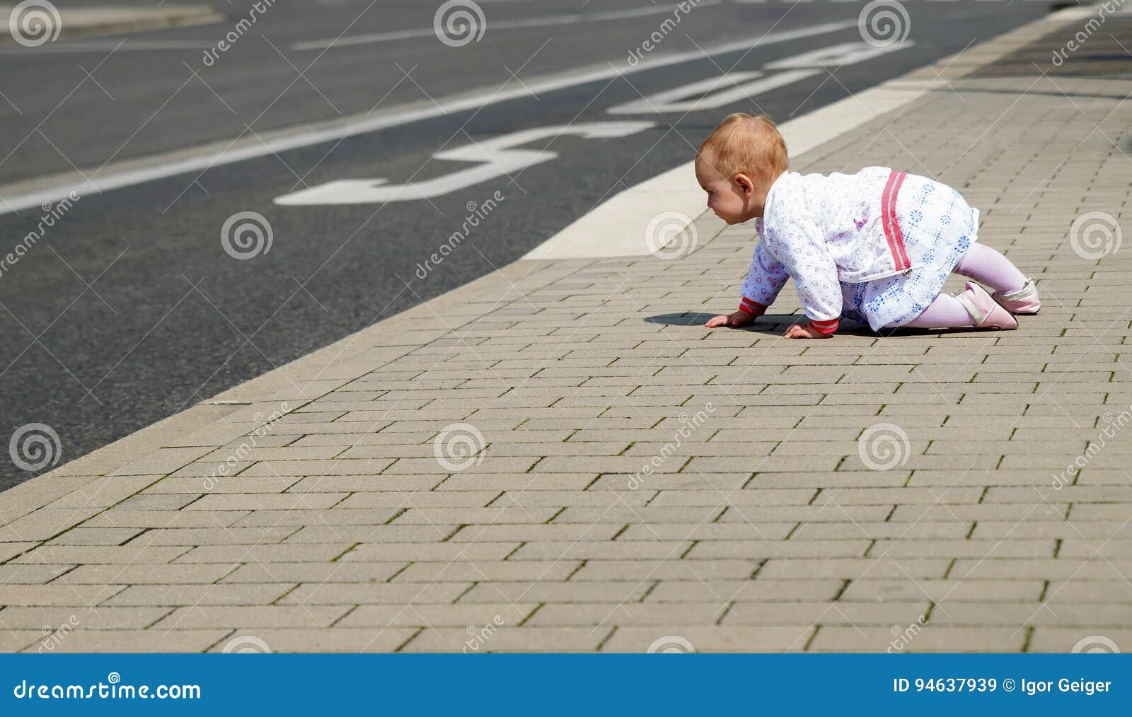 Kleines Baby in der weißen Kleidung, die entlang die Straße kriecht