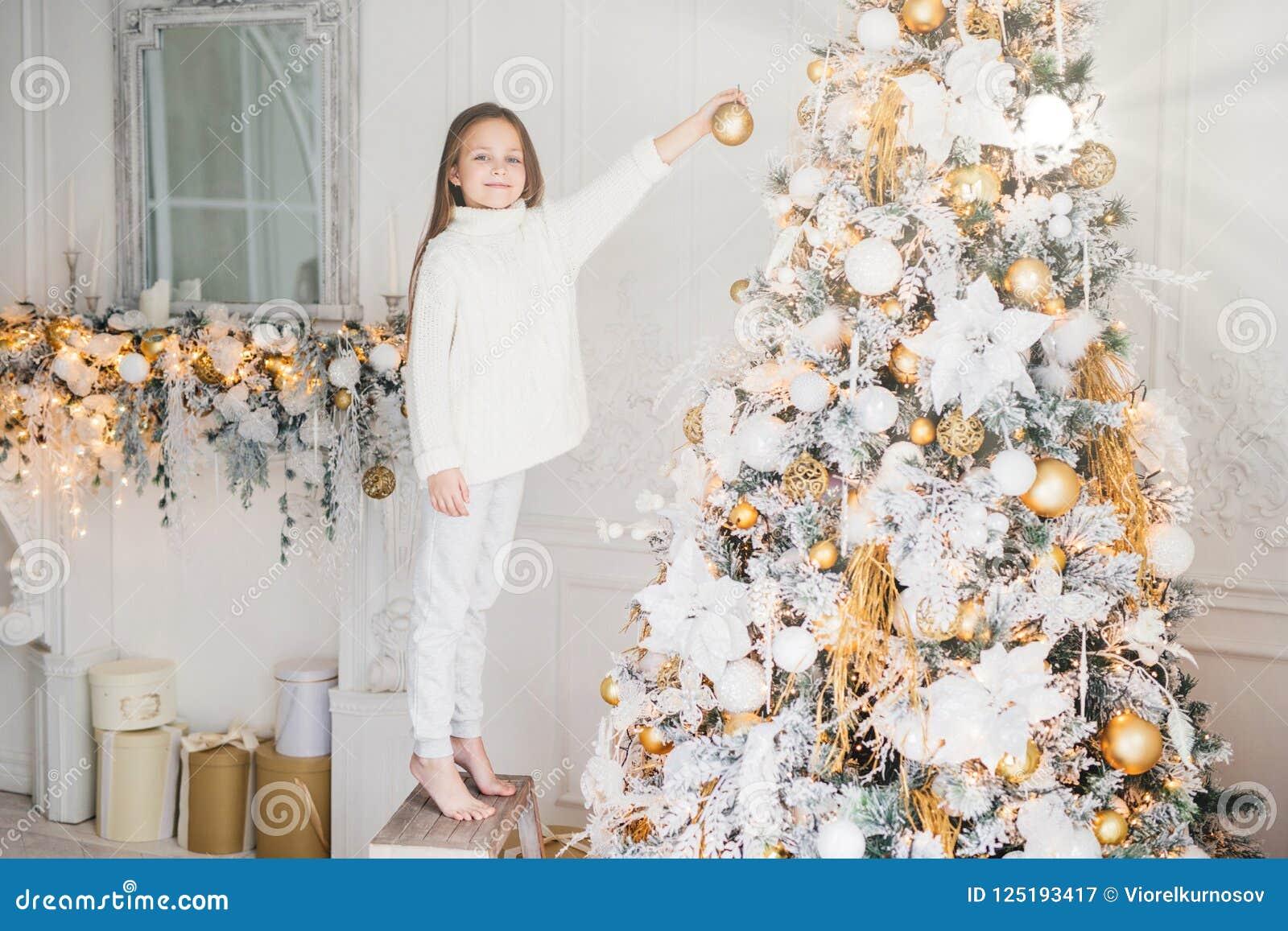 Kleines entzückendes weibliches Kind in der weißen Strickjacke und in der Hose hält Spielzeug für Dekoration, verziert Baum des n