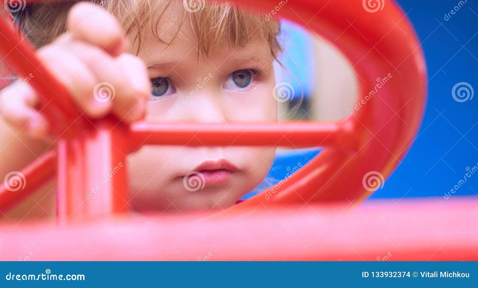 Kleines kaukasisches Baby sitzt am Steuer von einem Spielzeugauto Spielen auf dem Spielplatzkonzept
