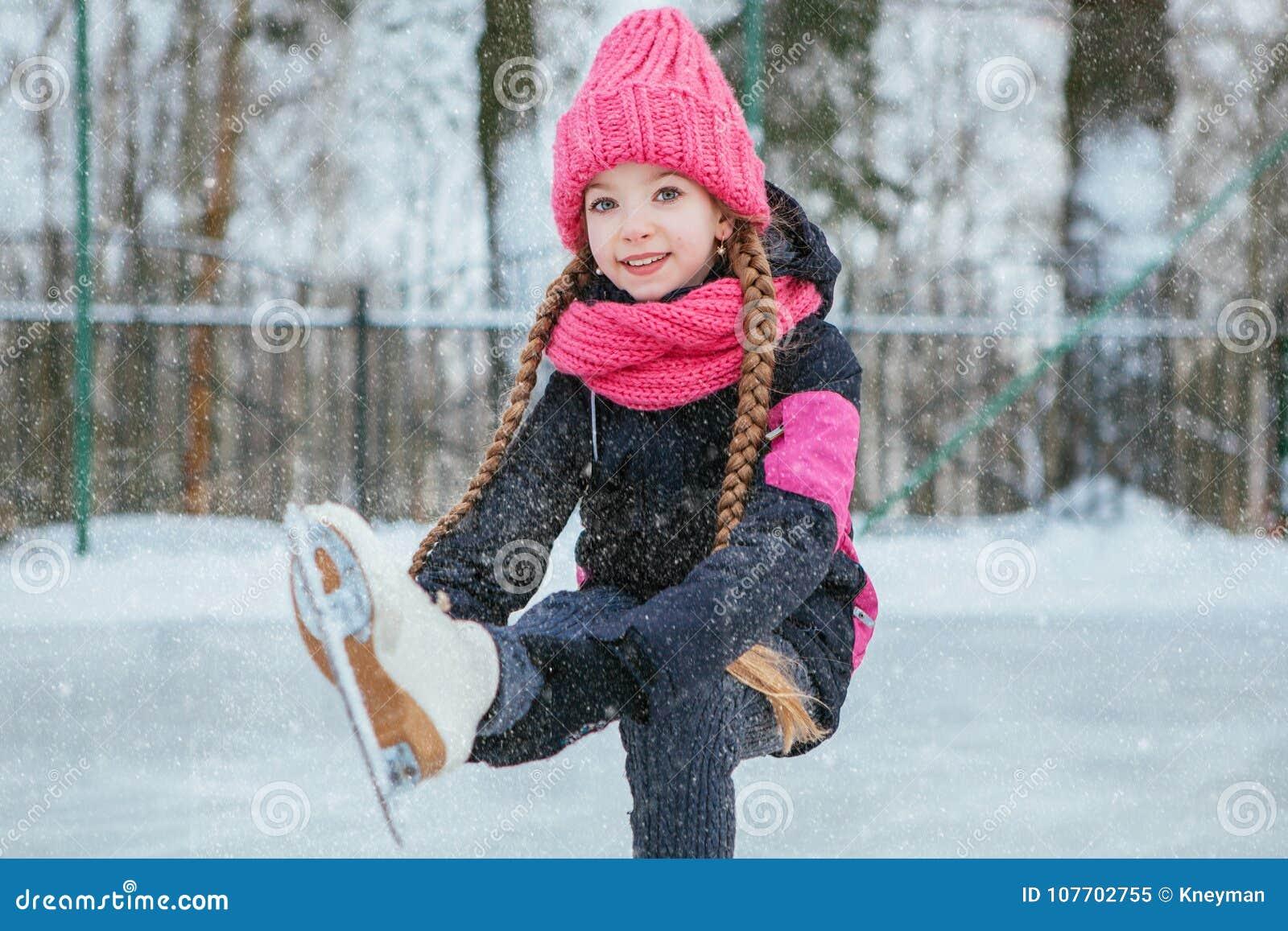 Kleines lächelndes Mädchen, das auf Eis in der rosa Abnutzung eisläuft Winter