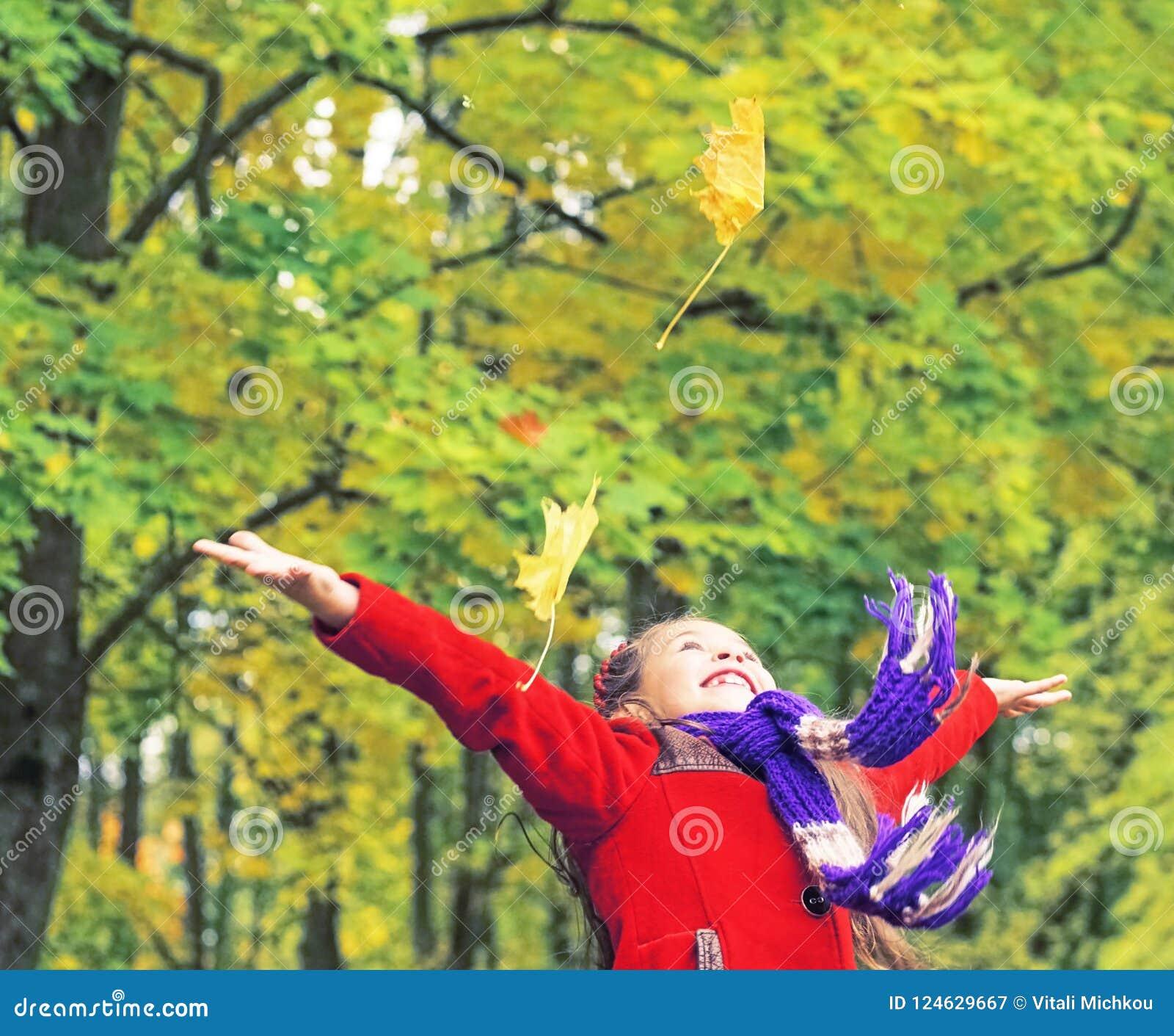 Kleines lachendes hübsches Mädchen im roten Mantel wirft gelbe Blätter im Herbstpark