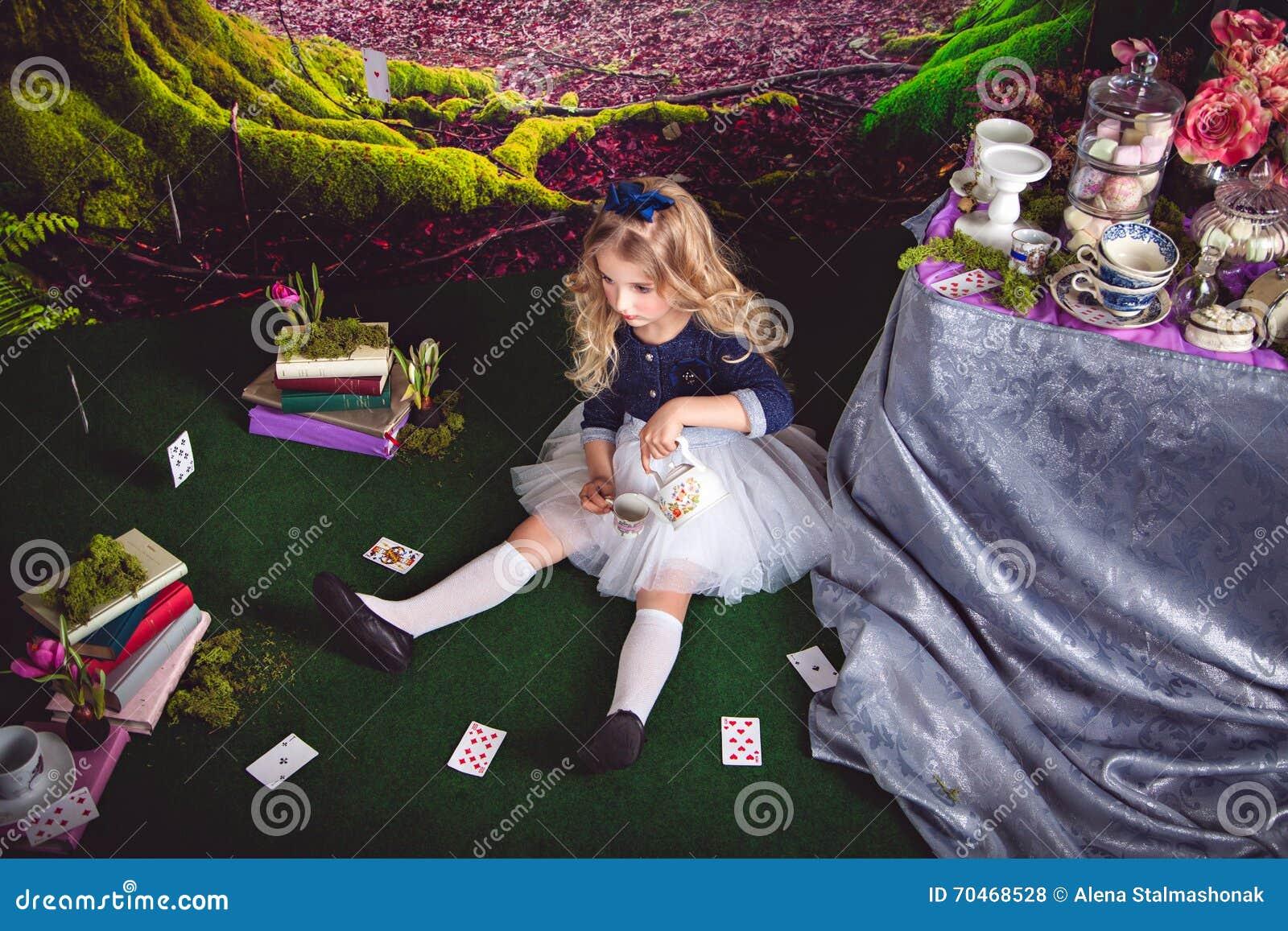 Kleines Mädchen als Alice in auslaufendem Tee des Märchenlandes