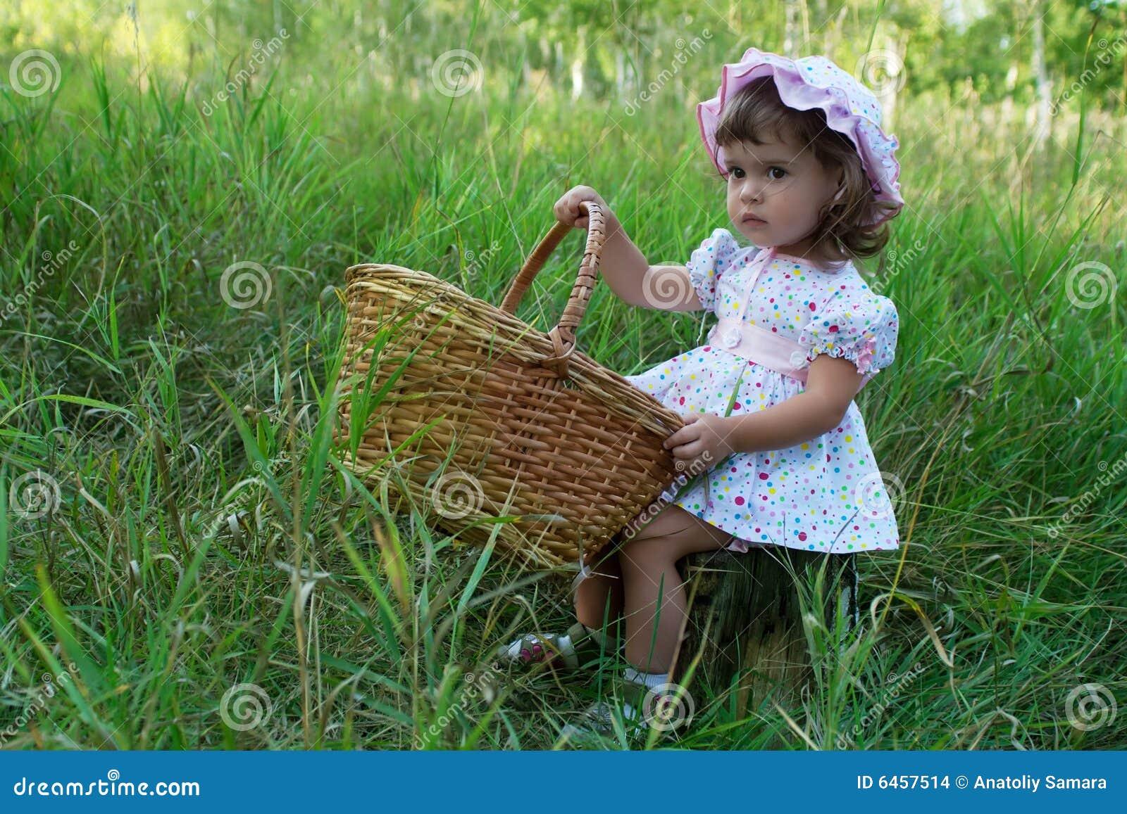 Kleines Mädchen, das auf einem Stummel sitzt und einen Korb anhält