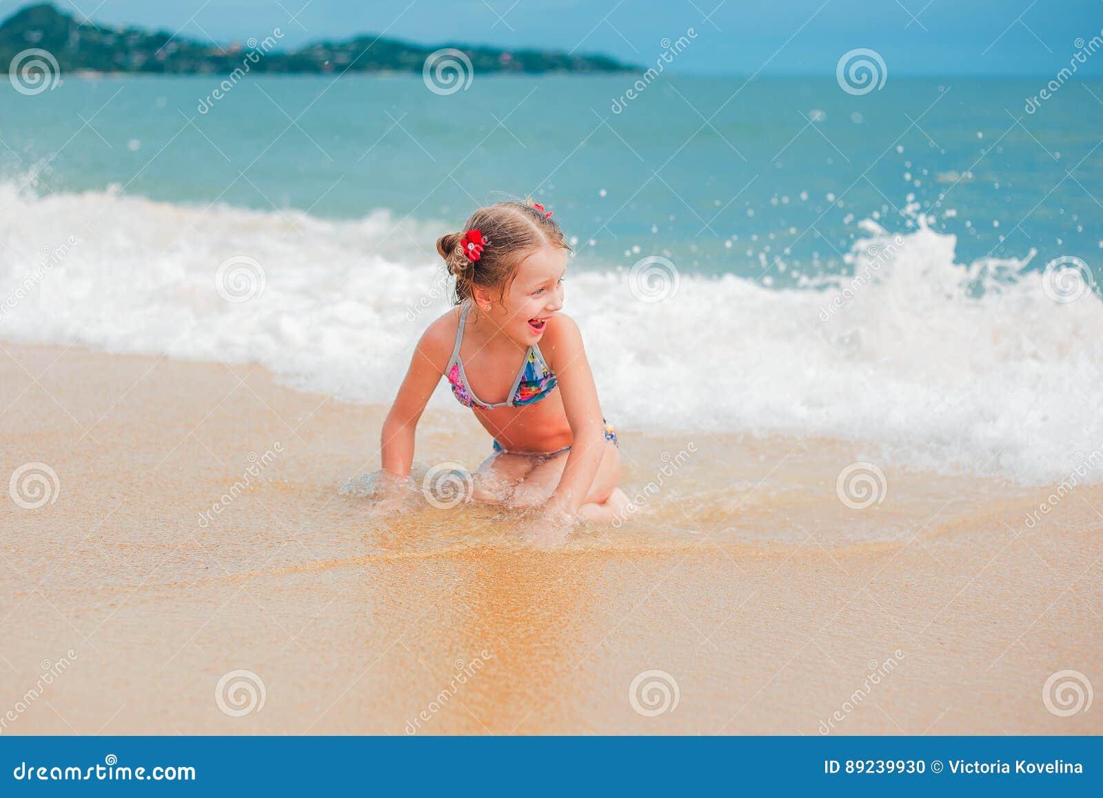 Kleines Mädchen, das auf Strand spielt