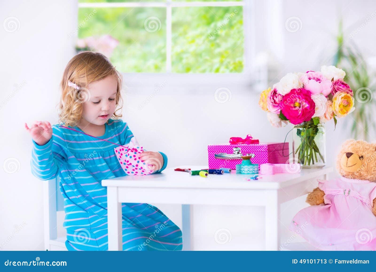 Kleines Mädchen, das ein Kleid für ihre Puppe näht