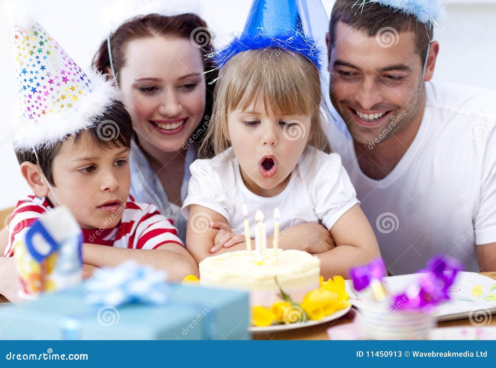 Kleines Mädchen, das heraus Kerzen in ihrem Geburtstag durchbrennt