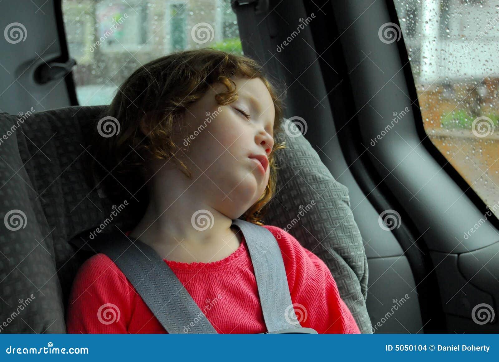 Ein kleines mädchen das in ihrem autositz an einem rainny tag
