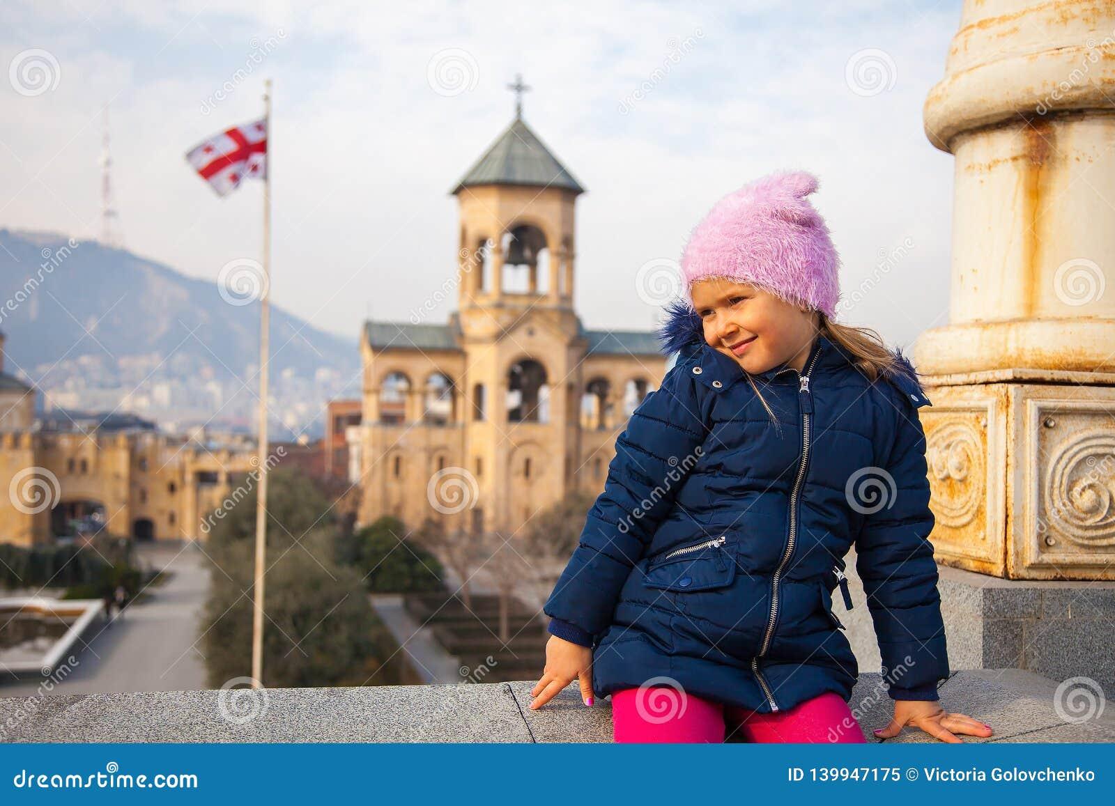 Kleines Mädchen, das im Kathedralenhof der Heiligen Dreifaltigkeit mit georgischer Flagge im Hintergrund seeting ist