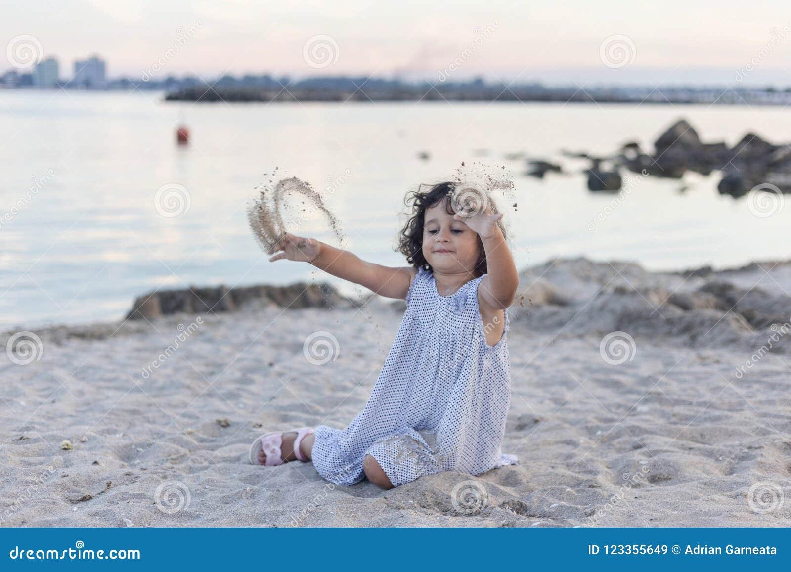 Kleines Mädchen, das im Sand an der Dämmerung spielt