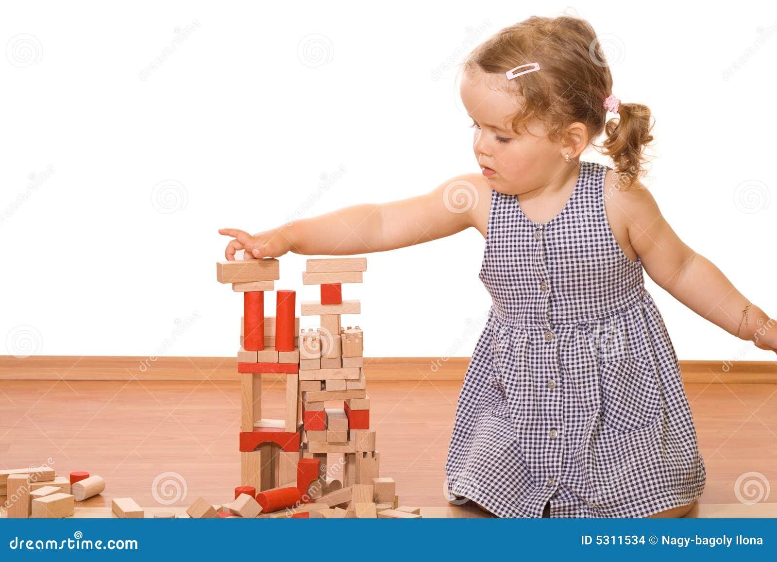 Kleines Mädchen, das mit hölzernen Blöcken spielt