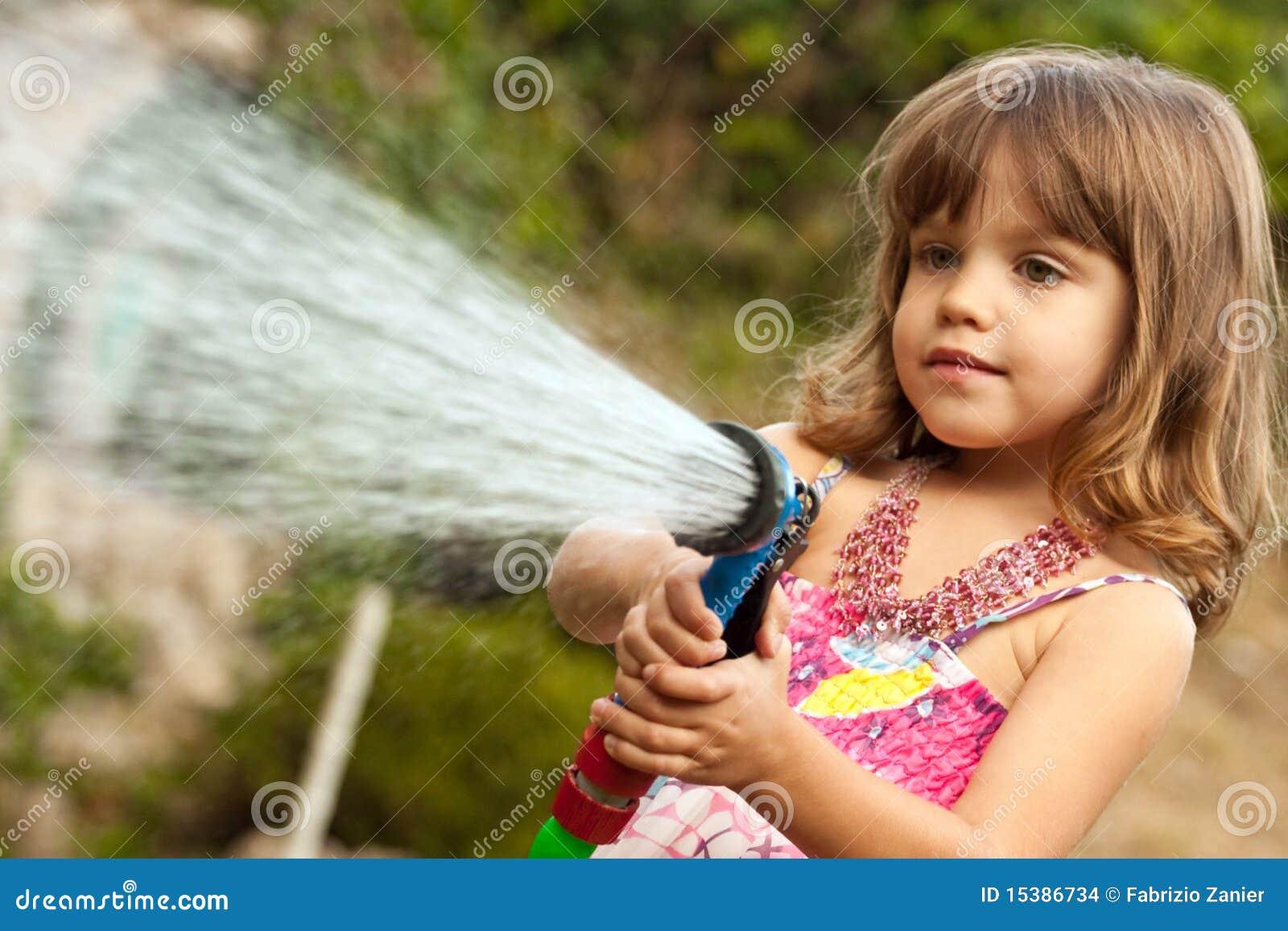 Kleines Mädchen, das mit Wasser spielt