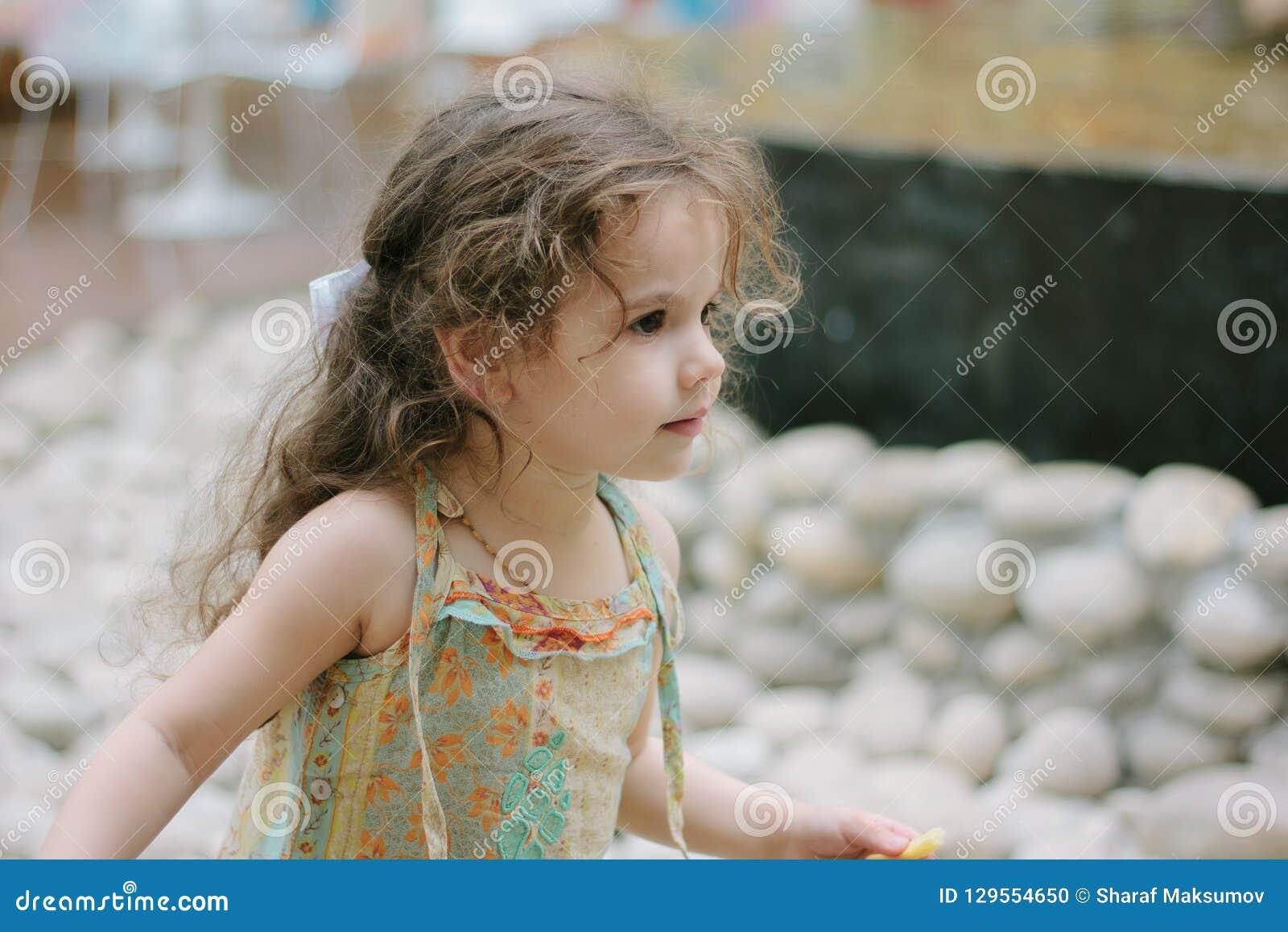 Kleines Mädchen, das Pommes-Frites am Café oder am Restaurant isst