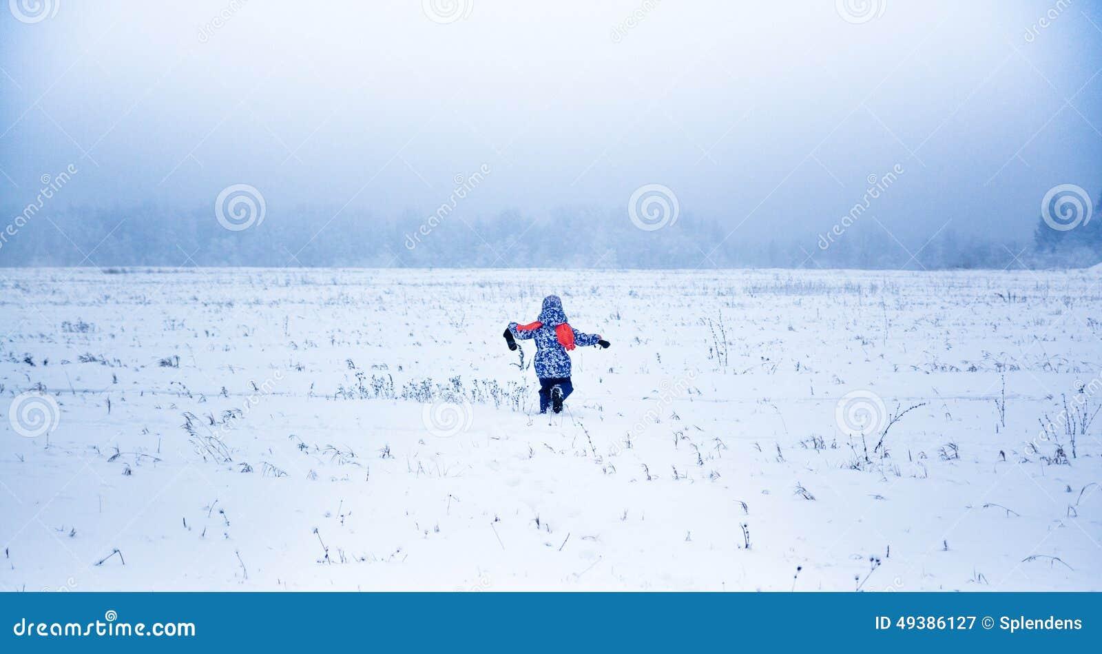 Kleines Mädchen, das weg in einen schneebedeckten Park läuft