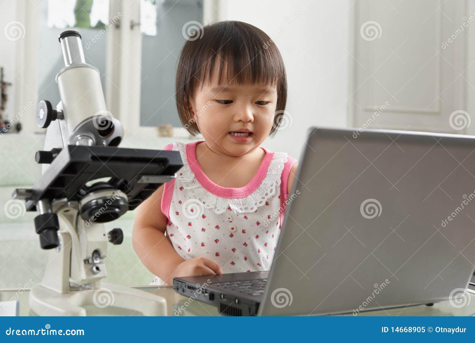 Kleines mädchen des genies mit laptop und mikroskop stockbild