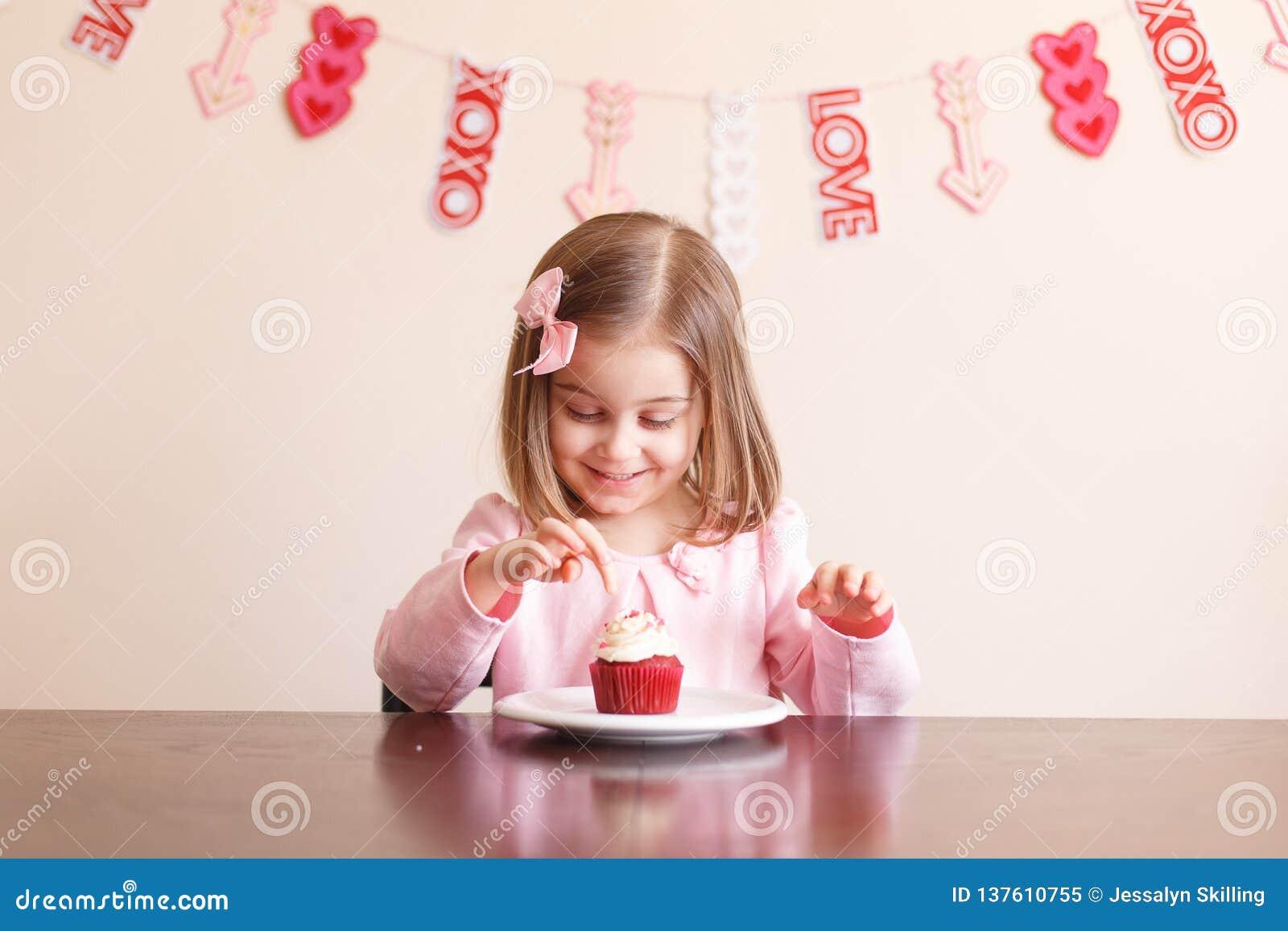 Kleines Mädchen des netten Valentinstags mit kleinem Kuchen