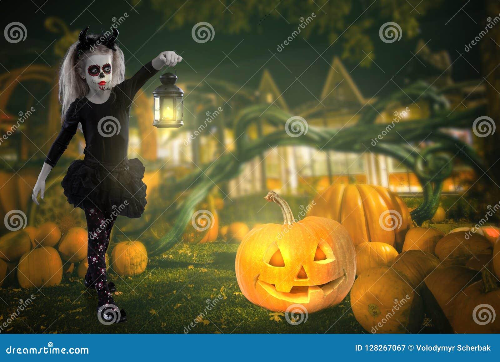 Kleines Mädchen in einem Kostüm der Hexe aufwerfend mit Kürbisen über feenhaftem Hintergrund Halloween