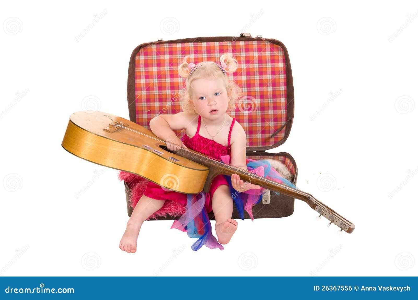 Kleines Mädchen in einem rosafarbenen Kleid, das Gitarre spielt