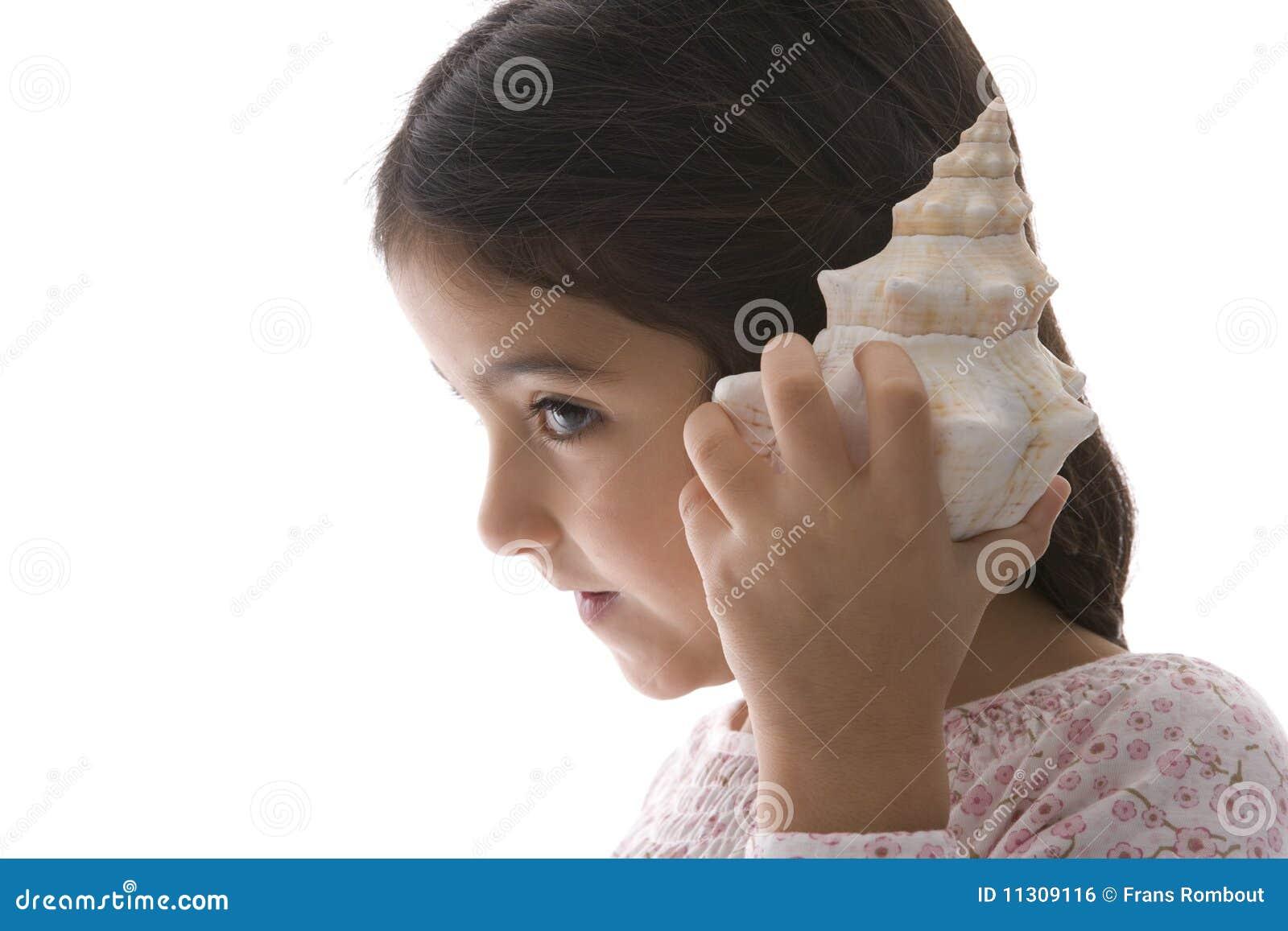 Kleines Mädchen hört zu einem großen Seeshell