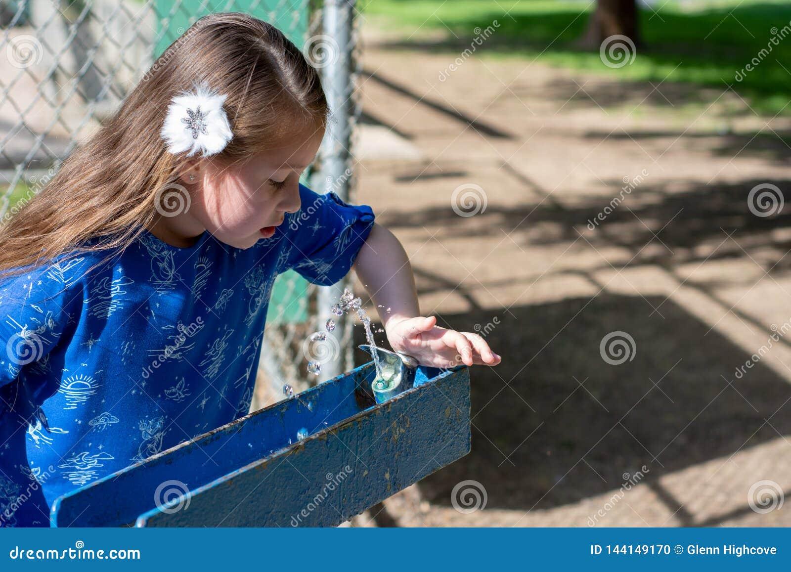 Kleines Mädchen im blauen Kleid unter Verwendung des Trinkbrunnens