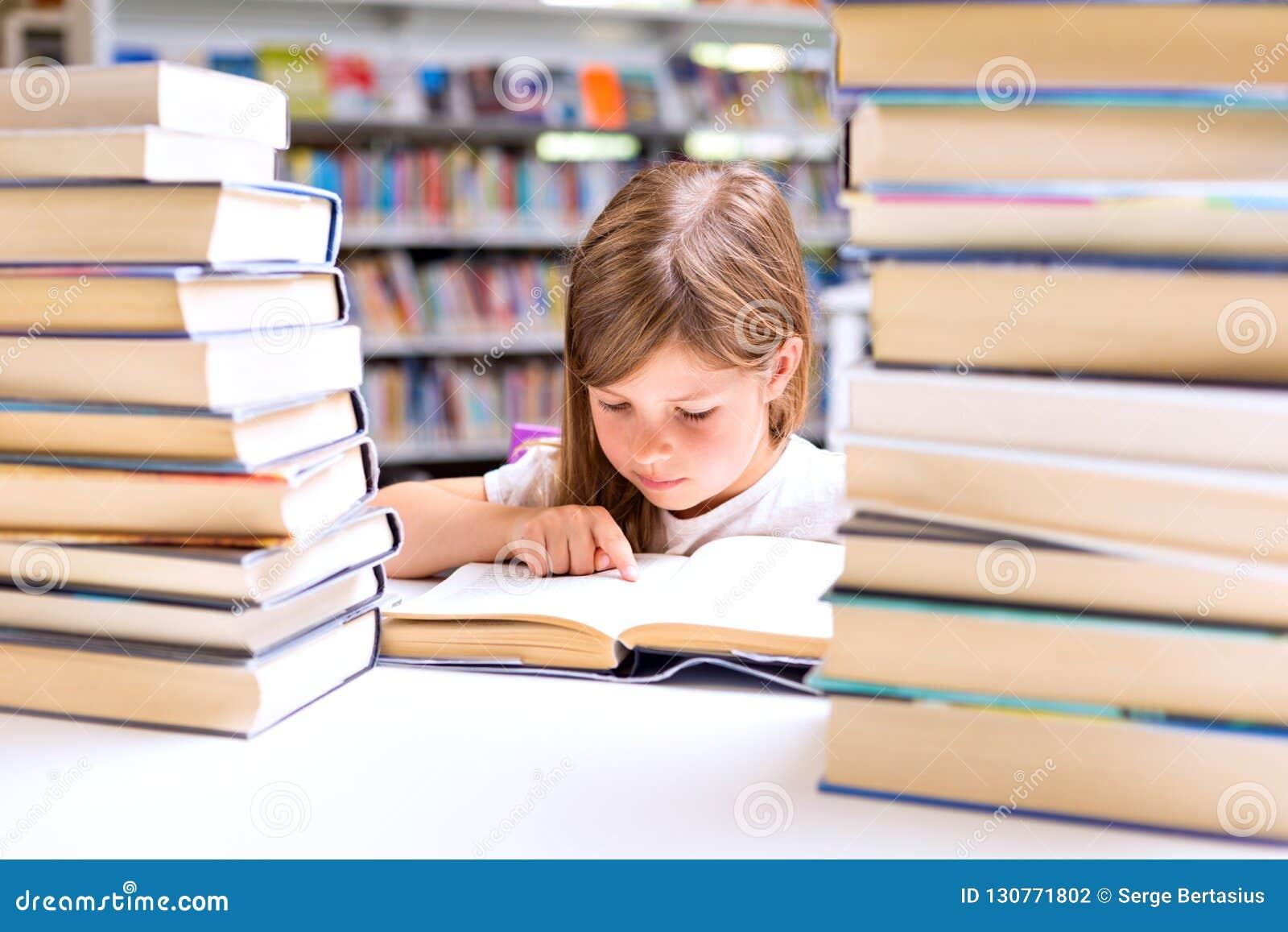 Kleines Mädchen liest ein Buch, das mit Stapel von Büchern in der Waage umgeben wird