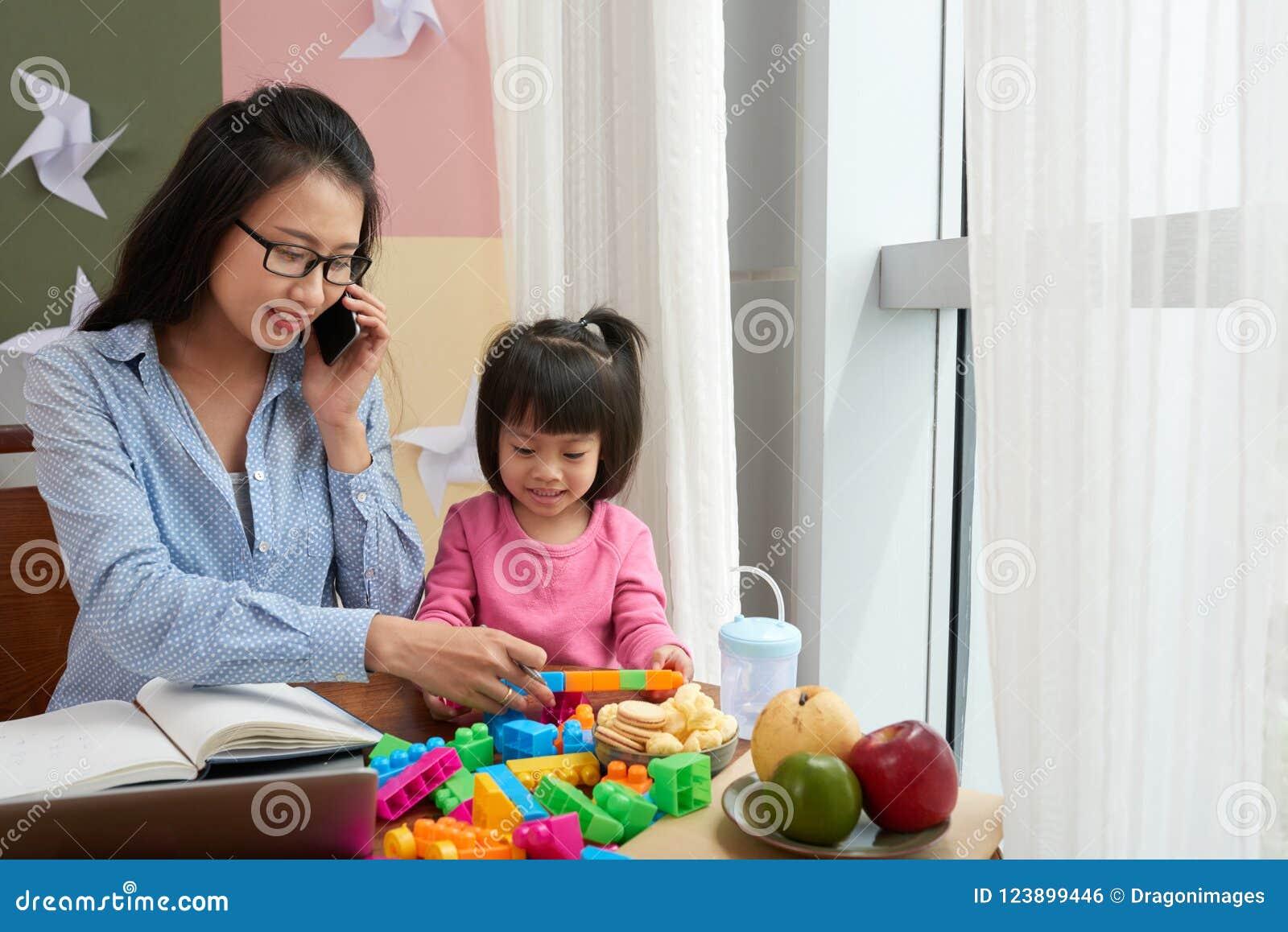Kleines Mädchen mit berufstätiger Frau zu Hause